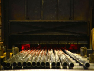 熱処理炉から出てきたばかりで炎が出ている鋼管の写真