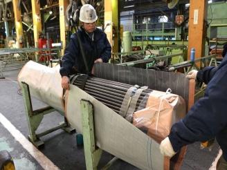 2人の作業員で丁寧に鋼管を梱包している写真